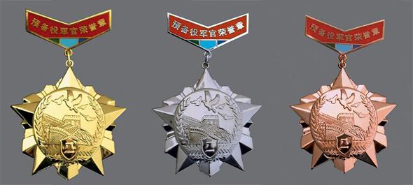 预备役军官金质荣誉章(左)、 银质荣誉章(中)和 铜质荣誉章(右) 图片:新华社发