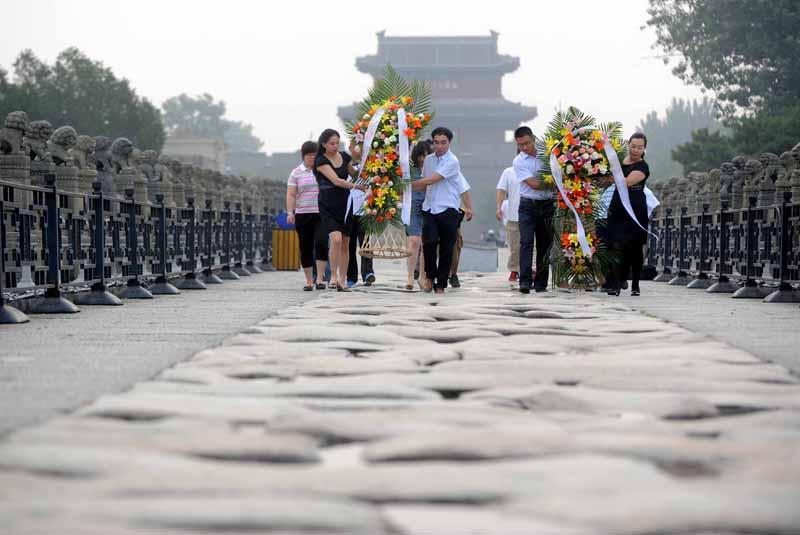 7月7日,参加活动的青年党员和团员在卢沟桥上摆放花篮。