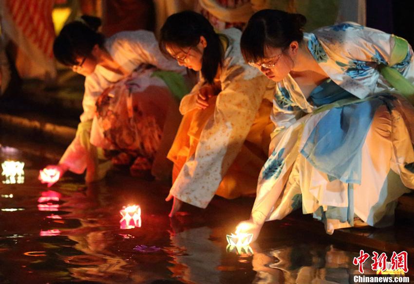 """南京汉服少女放荷灯迎""""七夕""""。8月11日晚,身着汉服的姑娘们在举行拜织女仪式。当晚,来自南京华夏文化传承社的近百名身着古汉服、头挽发髻的姑娘们走进社区,她们拜香案上香祭酒,与社区居民体验了""""晒书、乞巧、折荷灯、拜织女、魁星""""等各种精彩的内容,一起感受七夕节真正的含义和习俗。中新社发 泱波 摄"""