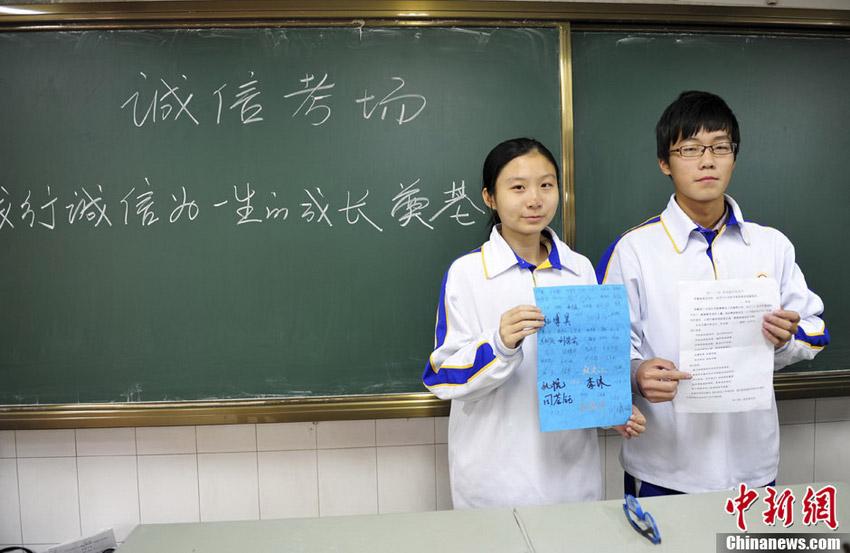 """11月12日,学生签署""""诚信公约"""",履行诚信考试承诺。中新社发 张勇 摄"""