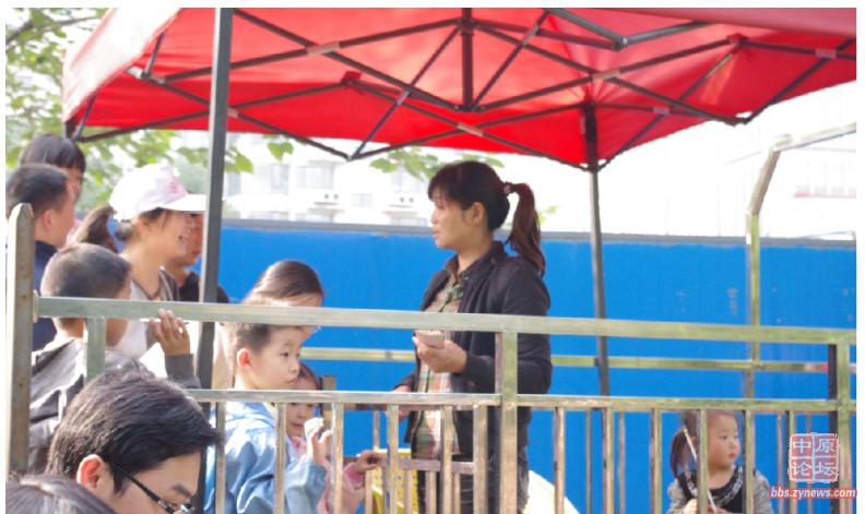 等待看熊猫的人排成了长龙,收费口收钱的工作人员手中拿着一沓钞票。(图片来源网络)