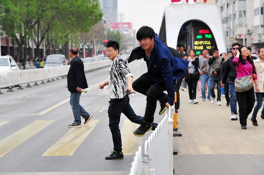 天空之城谱子李志-4月12日,在宁夏银川城区一条主干道上,几名行人在翻越交通安全护