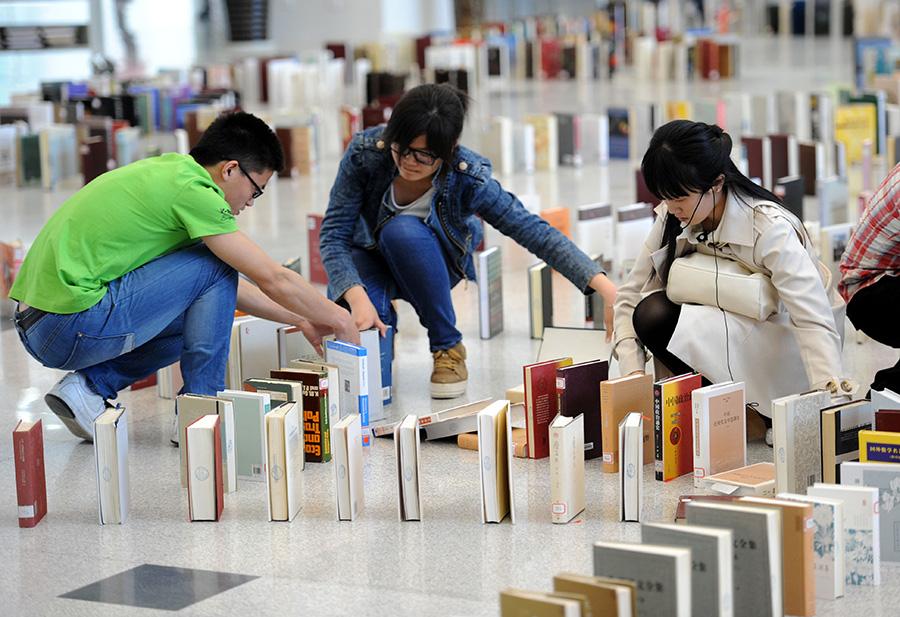 """4月23日,几名学生在摆放""""图书多米诺骨牌""""。新华社记者 孙参 摄"""