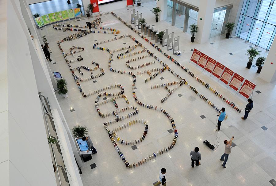 """4月23日,""""图书多米诺骨牌""""在图书馆大厅摆放完毕。新华社记者 孙参 摄"""