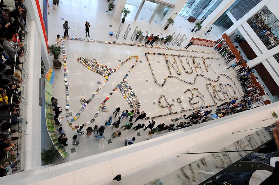 """4月23日,学生们在观看""""图书多米诺骨牌""""依次连续倒下。新华社记者 孙参 摄"""