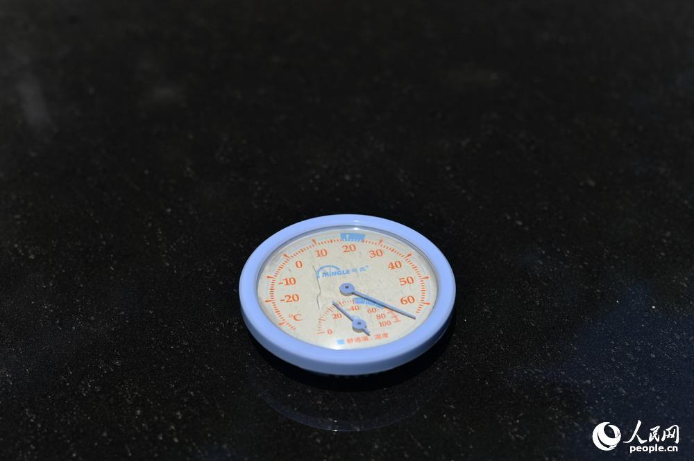 今日13时45分左右,记者将温度计放在汽车机盖上,瞬间超过极高清图片