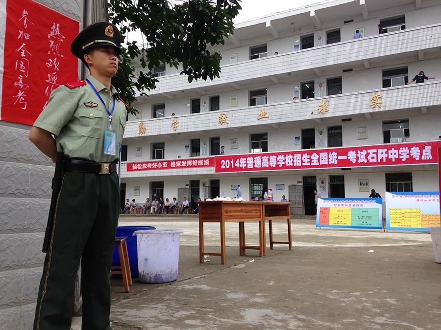 6月7日,贵州省暴雨洪涝重灾区石阡县石阡中学高考考点,一名刚从抢险救灾现场下来的武警战士投入到高考安保执勤工作中。新华社记者 闫起磊 摄