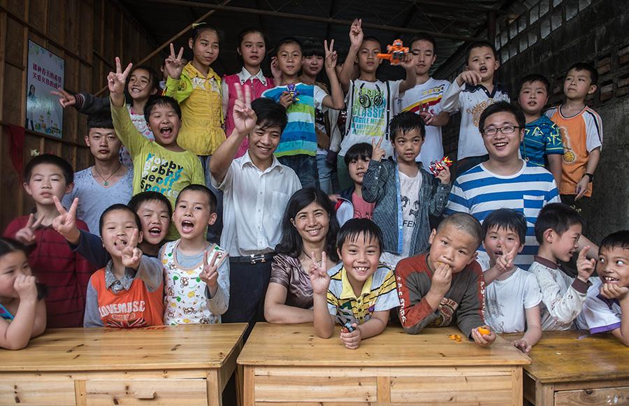 """王雪娟(前中)、""""东篱之家""""志愿者与留守儿童合影(5月25日摄)。新华社记者韩传号摄"""