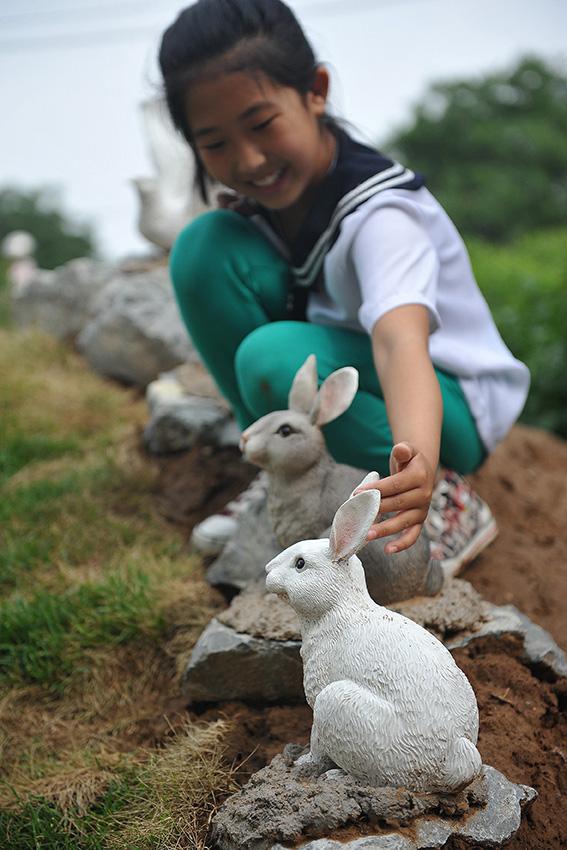 """6月10日,在辽宁省朝阳市辽河小学""""动植物园""""里,一名学生在欣赏动物塑像。新华社发(白铁军 摄)"""