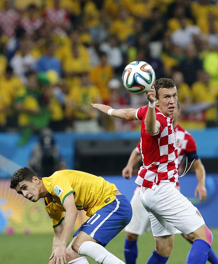 当地时间6月12日,巴西队球员奥斯卡(左)与对方球员拼抢。新华社记者周磊摄