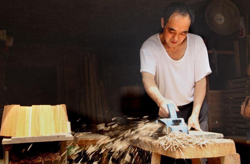 圆木匠余兴华在利用传统圆木制桶工艺刨制圆形木制