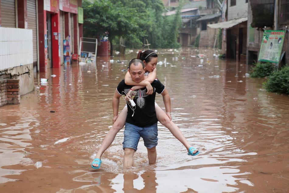7月7日,四川省内江市东兴区田家镇居民涉水出行.