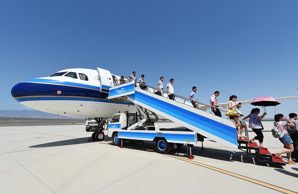南航湖南分公司的空客a320飞机降落在吐鲁番机场,乘客走出机舱.