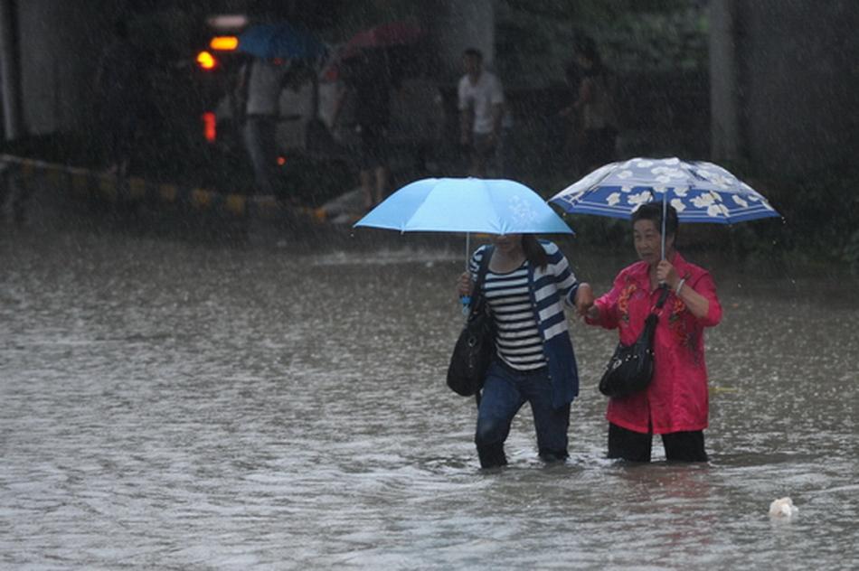 欧东/7月16日,两位贵阳市民涉水经过积水路段。新华社记者欧东衢摄