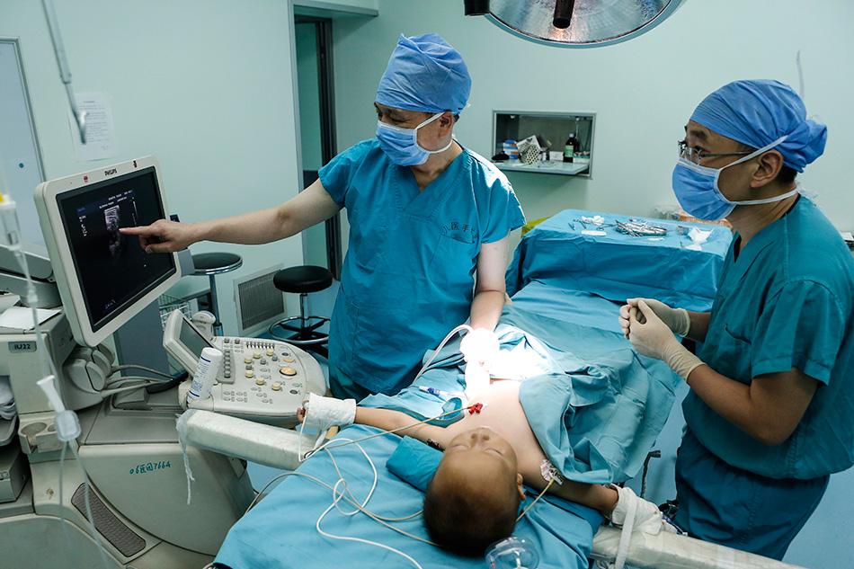 北京儿童医院超声科主任贾立群在手术室内为患儿做超声复查(7月18日摄