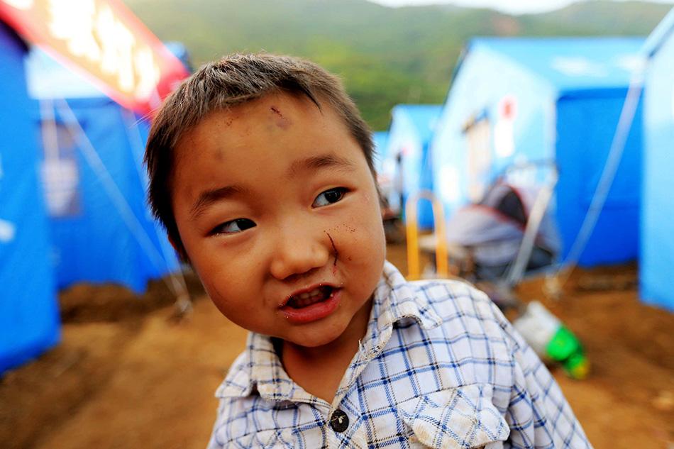 8月6日,今年3岁的小朋友戴英峰在安置点前玩耍