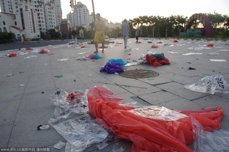 2014年8月11日,海南琼海,万泉河喷泉广场晨练的人们踩着塑料垃圾行走.