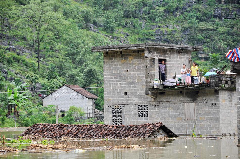 8月13日,广西都安县保安乡巴善村的几名村民被洪水围困,等待救援.