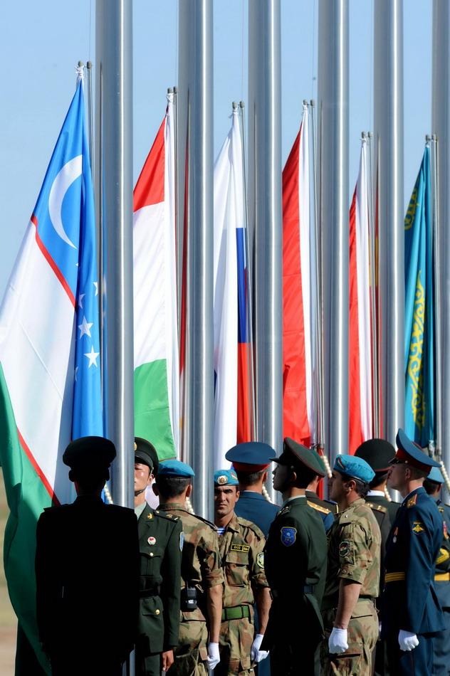 """8月24日,在内蒙古朱日和训练基地,各国参演部队旗手在""""和平使命—2014""""联合反恐军事演习开始仪式上升起各成员国国旗。"""
