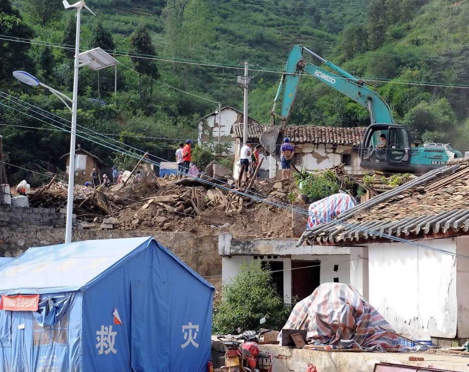 云南鲁甸地震中,许多当地群众的房屋成为废墟.在党和政府的帮助图片