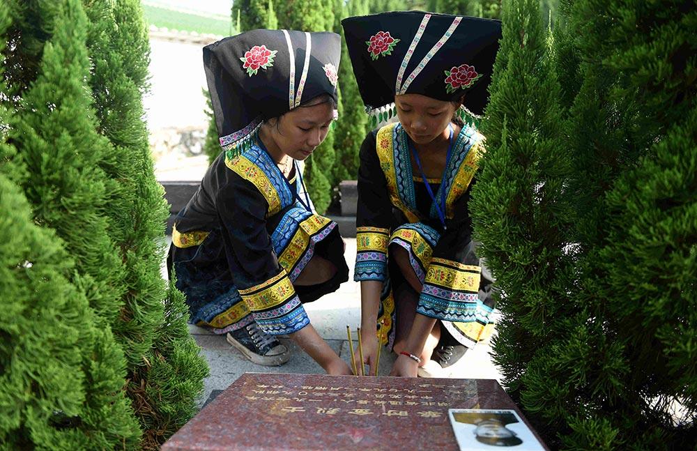 【各地举行烈士纪念日活动】:9月30日,两名壮族少女在广西宁明县烈士陵园祭拜革命烈士。新华社记者张爱林摄