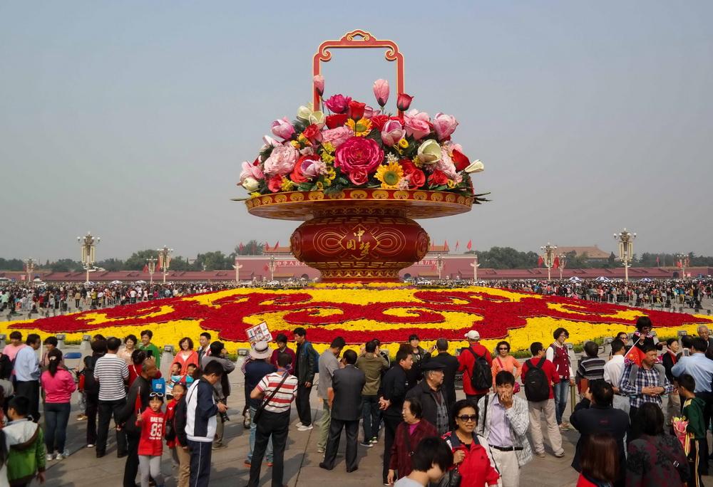 """10月7日,游客在天安门广场的""""大花篮""""周围合影留念。新华社记者 罗晓光 摄"""