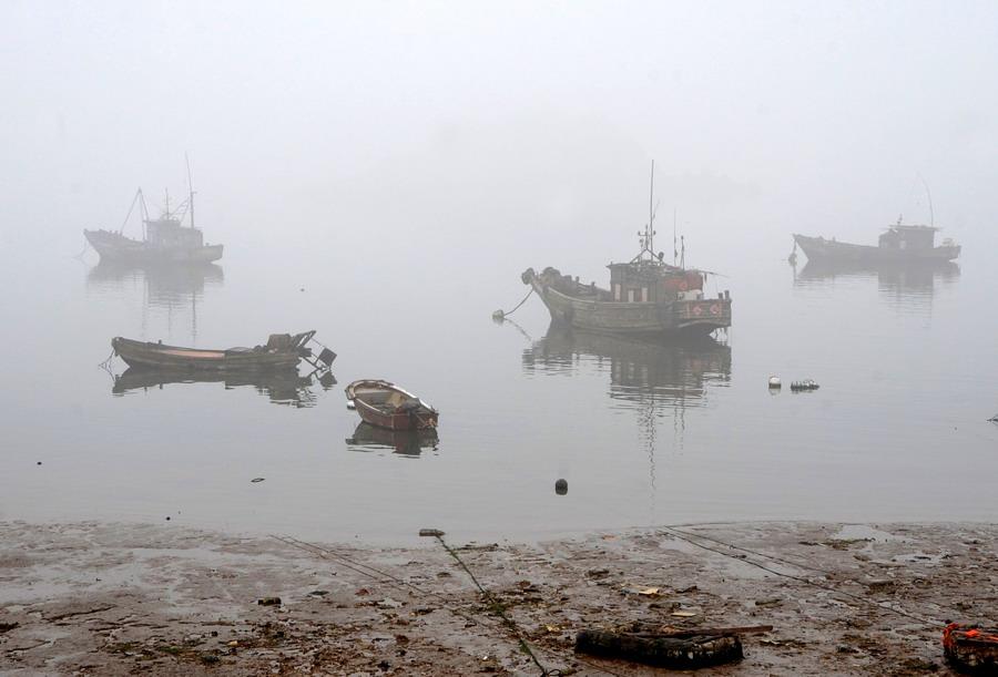 3月17日清晨,在江苏连云港海边,渔船在雾中若隐若现.