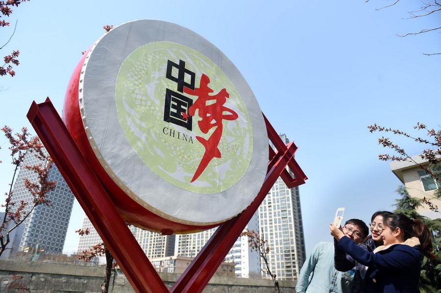 """居民在""""中国梦""""大鼓主题雕塑旁驻足."""