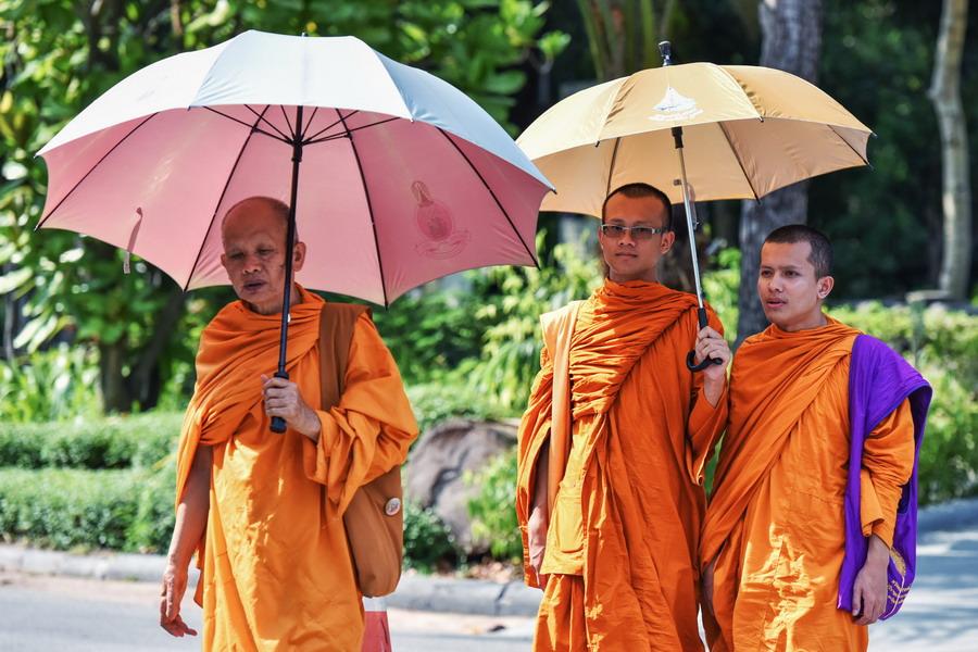 4月22日,僧人撑伞游览泰国曼谷律实动物园.新华社记者 李芒茫 摄