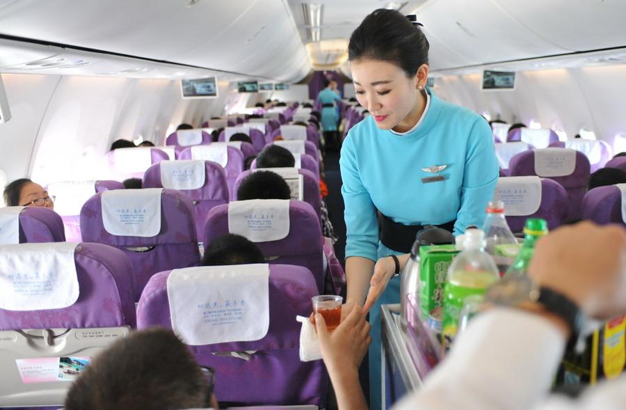 乘务员侯昳偲在飞机上为乘客服务(4月30日摄)