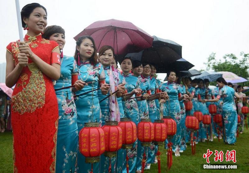 """5月16日,中国旗袍会湖南总会的千名会员们在长沙橘子洲沙滩公园举行""""世界吉尼斯旗袍秀""""。主办方表示,当日,中国旗袍会在全球近300个分会场引领近10万华人佳丽身着典雅的旗袍,行走在中国大地和全球各个地方,挑战身着旗袍人数最多的吉尼斯世界纪录。杨华峰 摄"""