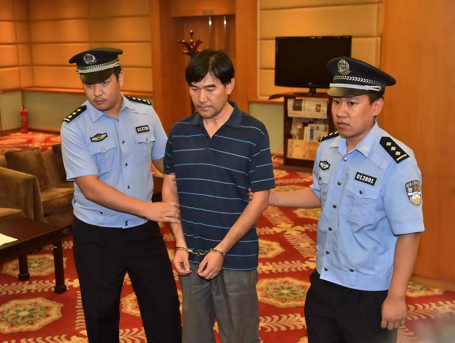 6月8日,孙新被押解回国,并在检方宣读《逮捕决定书》后被戴上手铐。新华社记者 李文 摄