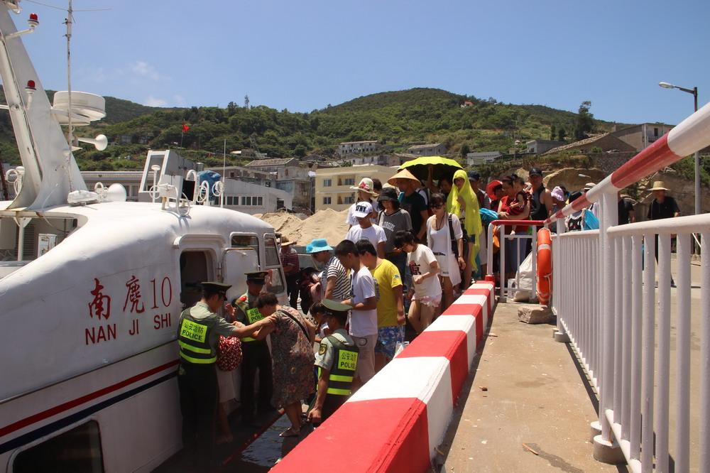 8月6日,在浙江温州南麂岛,边防官兵帮助游客登上快艇,准备撤离.