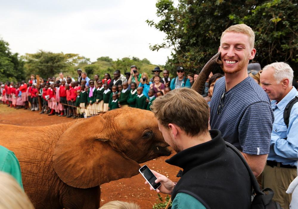 """8月6日,在肯尼亞內羅畢市郊的""""大象孤兒院"""",一名游客被小象""""親吻""""。"""