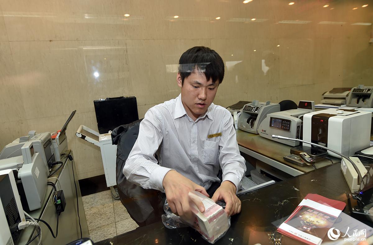 2015年11月12日,2015年版第五套人民币100元纸币发行开始在全国发行。图为工商银行员工整理新版百元人民币。(人民网记者 翁奇羽/摄影)