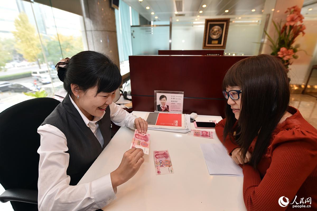 2015年11月12日,2015年版第五套人民币100元纸币发行开始在全国发行。图为工商银行工作人员向储户介绍新旧百元人民币的区别与防伪常识。(人民网记者 翁奇羽/摄影)
