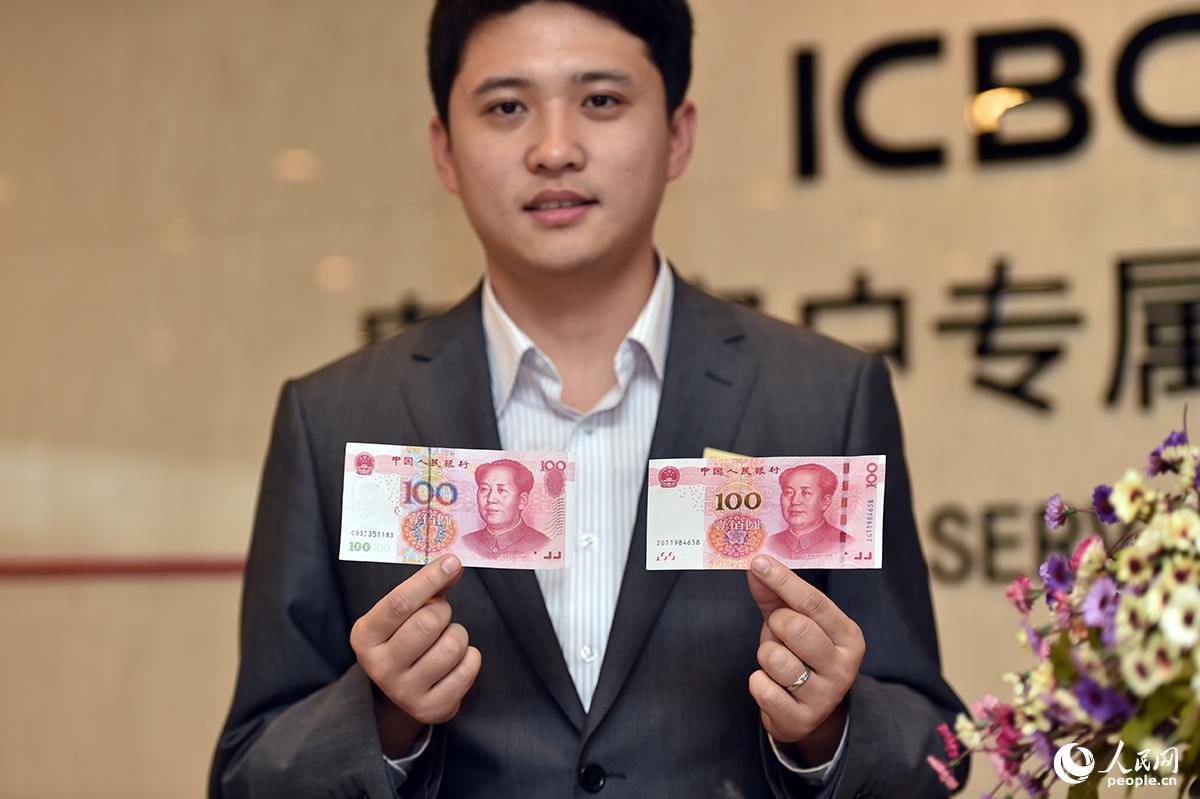 2015年11月12日,2015年版第五套人民币100元纸币发行开始在全国发行。图为工商银行工作人员展示新旧百元人民币,右手为旧版百元人民币左手为新版百元人民币。(人民网记者 翁奇羽/摄影)
