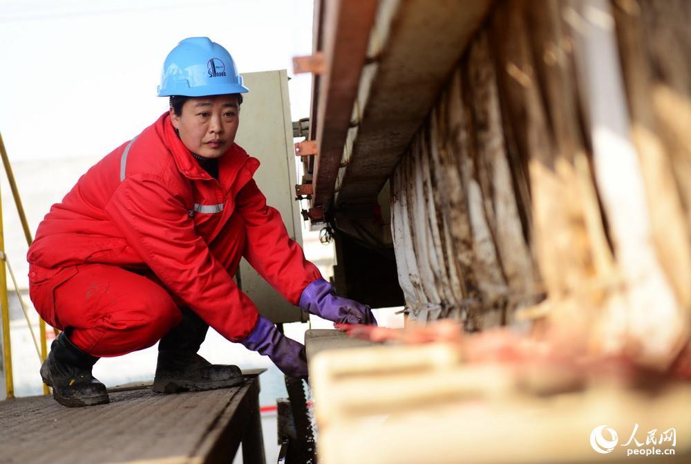 华玲对工作认真负责,及时对处理设备的闸门进行检查,确保设备的安全运行。图为:华玲在检查泥浆处理设备的排水闸门。
