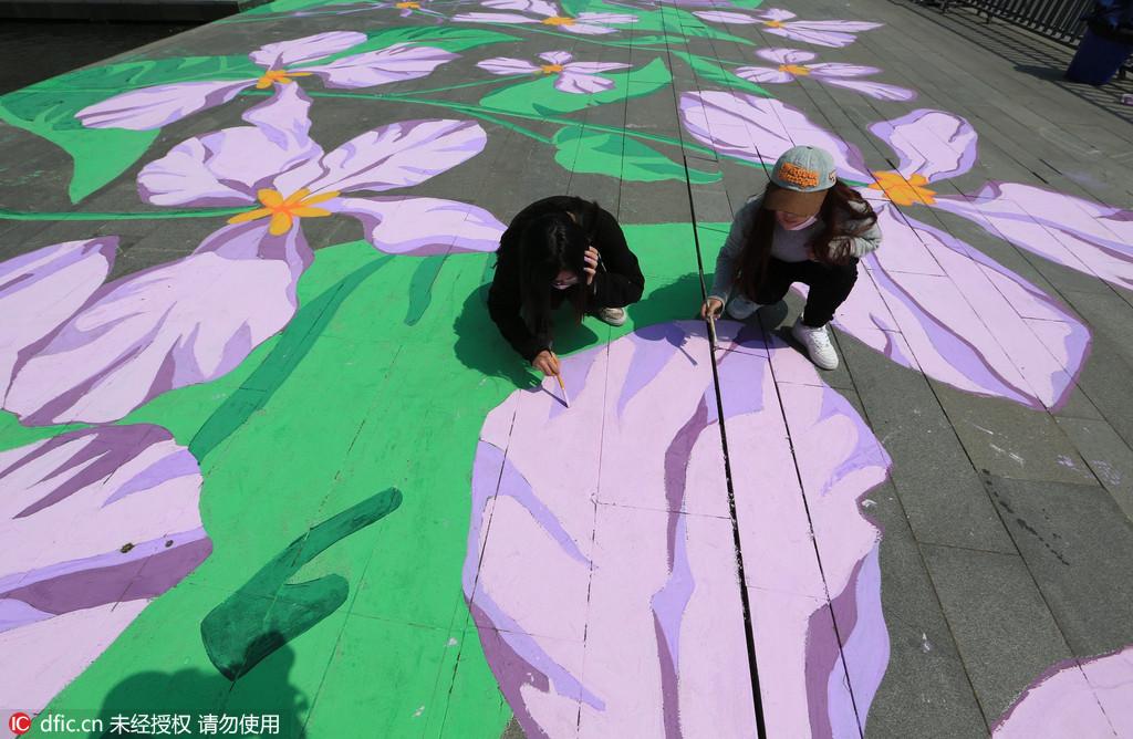 """用美术颜料手绘紫金草图案,将这和平之花亲手""""种植""""在了纪念馆雕塑"""