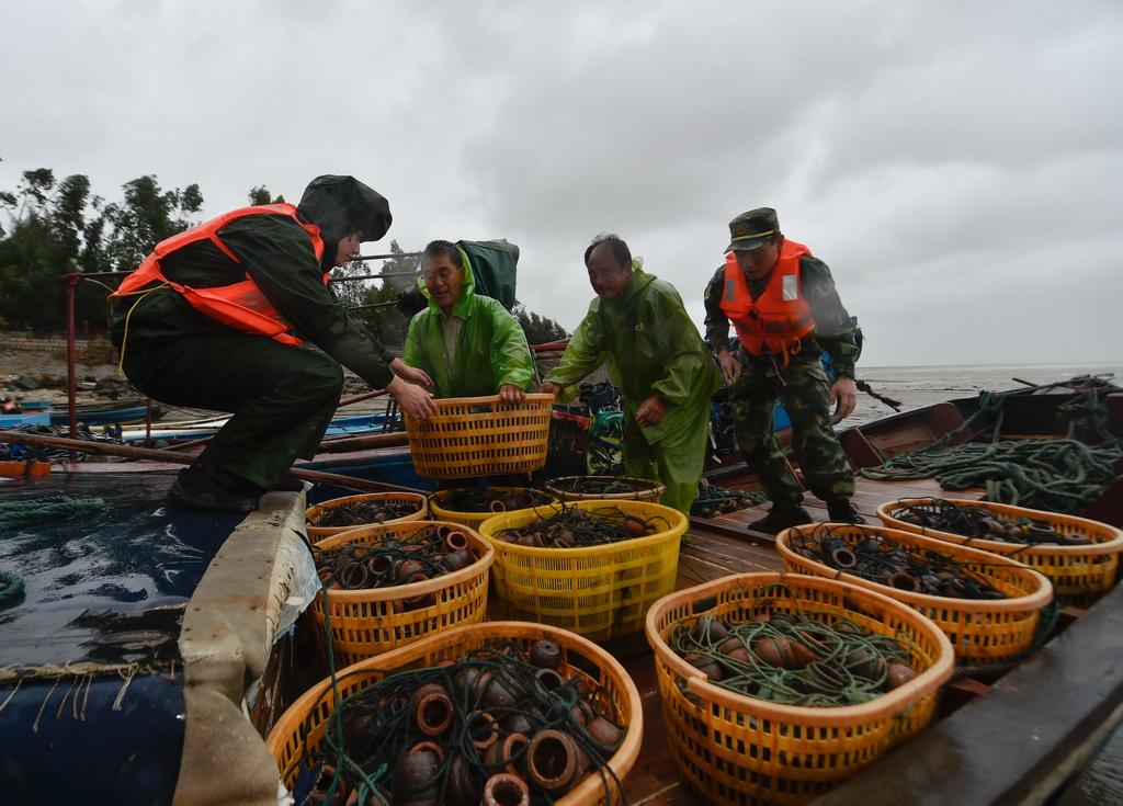 9月27日,福州边防支队官兵在福州福清市龙田镇东壁岛码头帮助渔民转移渔具。 新华社记者 宋为伟摄