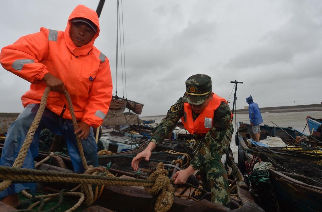 9月27日,福州边防支队民警在福州福清市龙田镇东壁岛码头帮助渔民加固渔船。新华社记者 宋为伟摄