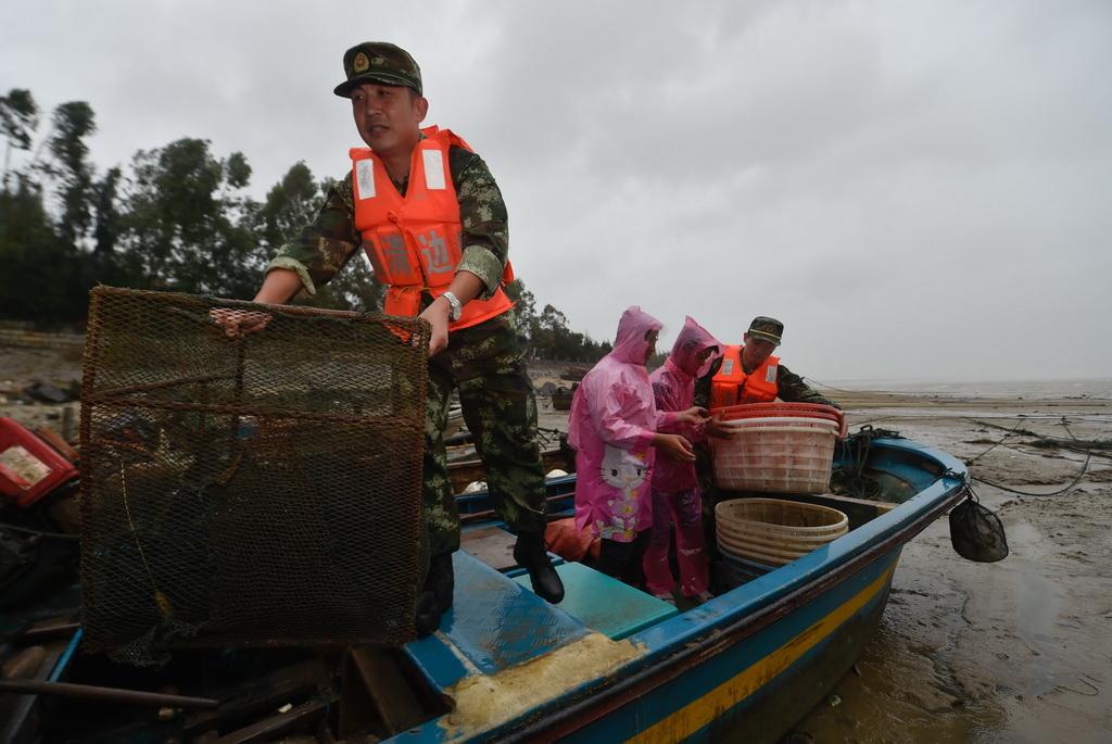 9月27日,福州边防支队官兵在福州福清市龙田镇东壁岛码头帮助渔民转移渔具。新华社记者 宋为伟摄
