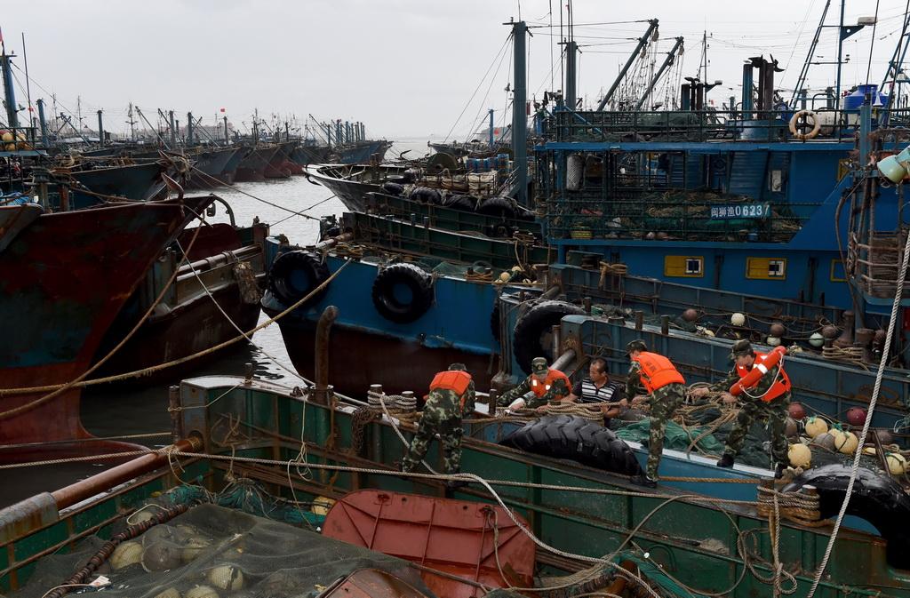 9月27日,泉州边防支队祥芝边防派出所官兵在福建石狮祥芝中心渔港帮助渔民加固船只。 新华社记者 姜克红摄