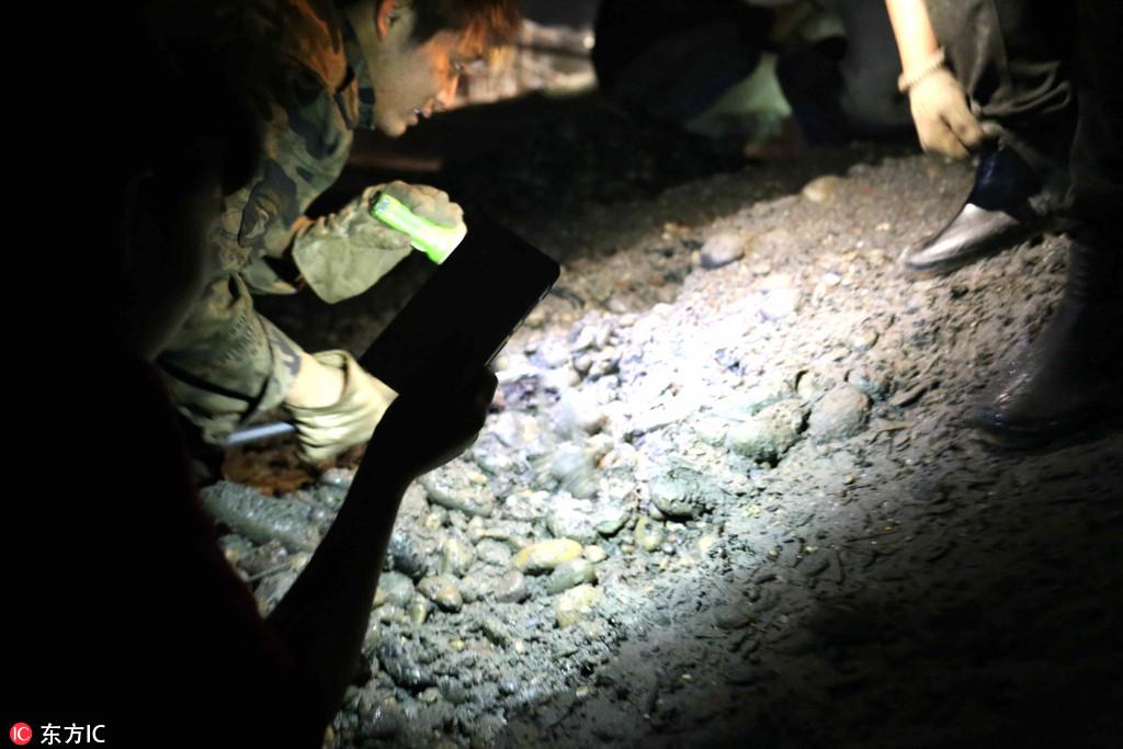 2016年10月18日,重庆江北区长石尾码头,市民们戴着手套、嘴叼电筒,在夜色下用铁篱笆挖宝藏。近日,重庆江北区的长石尾码头上突然变得热闹非凡,每天都有上百人在这里忙着挖宝藏。挖宝的人群中有的拿锄头铁镐,有的拿钉耙木棒,大家的目标就是藏在鹅卵石堆里印有嘉庆通宝字样的的铜钱。据悉,这些刚刚运到长石尾码头的鹅卵石是从长江河道里挖出来的,里面夹杂着不少铜钱。