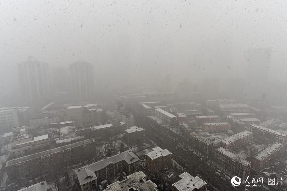 2月21日中午,北京城区飘起鹅毛大雪,能见度下降,窗外的央视大楼以及中国尊基本无法看清。(人民网记者 翁奇羽 摄)