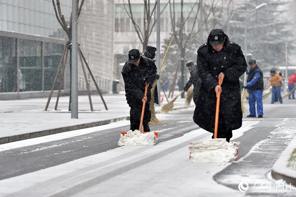 2月21日中午,北京城区飘起鹅毛大雪,工作人员清理路面上的积雪。(人民网记者 翁奇羽 摄)