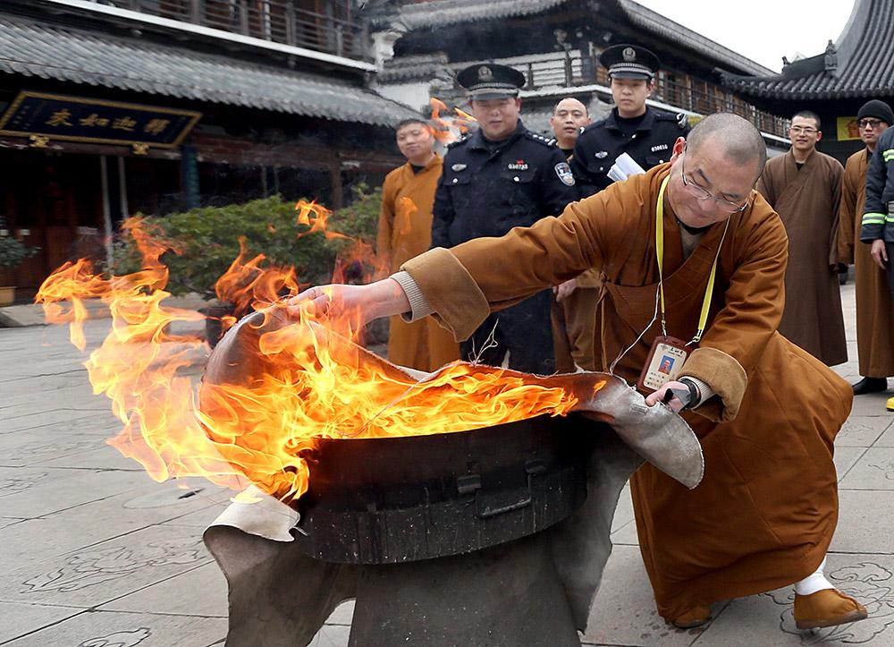 2月22日,法师消防队队员在民警指导下使用灭火毯进行灭火训练.