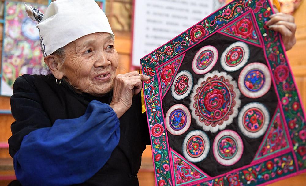 现年91岁的侗族老人覃奶时清,是广西三江侗族自治县同乐苗族乡同乐村平溪屯人,她自幼学习剪纸,嫁入民间技艺世家覃姓人家后,深入学习裁缝、剪纸、刺绣等手工技艺,曾多次参加民间民族手工艺品大赛并获奖。 在她的影响和引导下,她的两个儿媳杨甜、韦清花不断努力研究和学习侗族刺绣等民间手工技艺,并先后成为广西壮族自治区非物质文化遗产项目(侗绣)代表性传承人。 覃奶时清老人目前身体硬朗,有空就到村里走走,把这门技艺毫不保留地传授给村里的妇女和孩子们。新华社记者陆波岸摄