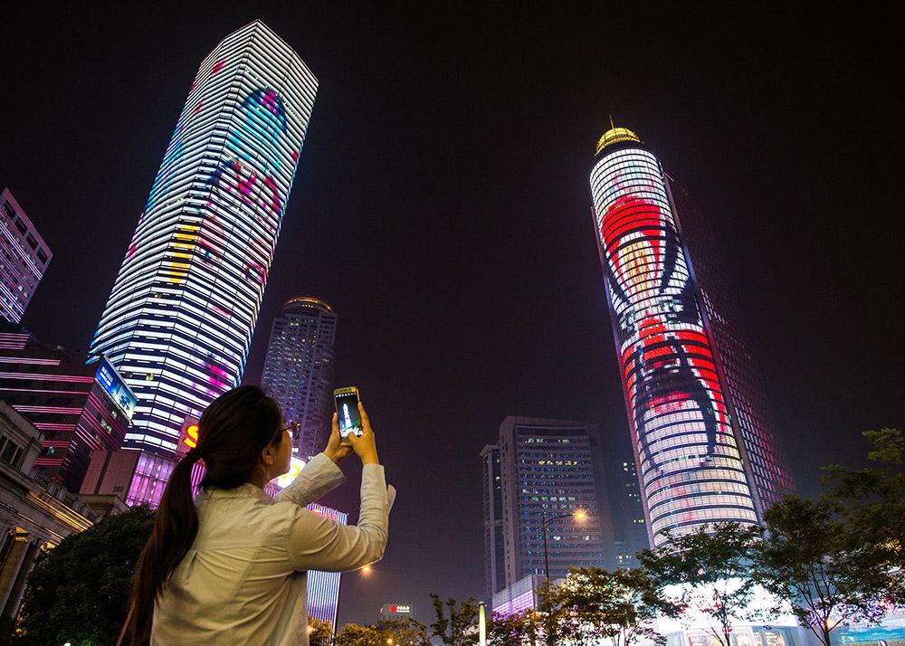 5月6日,市民在南京新街口拍摄京剧脸谱灯光秀.