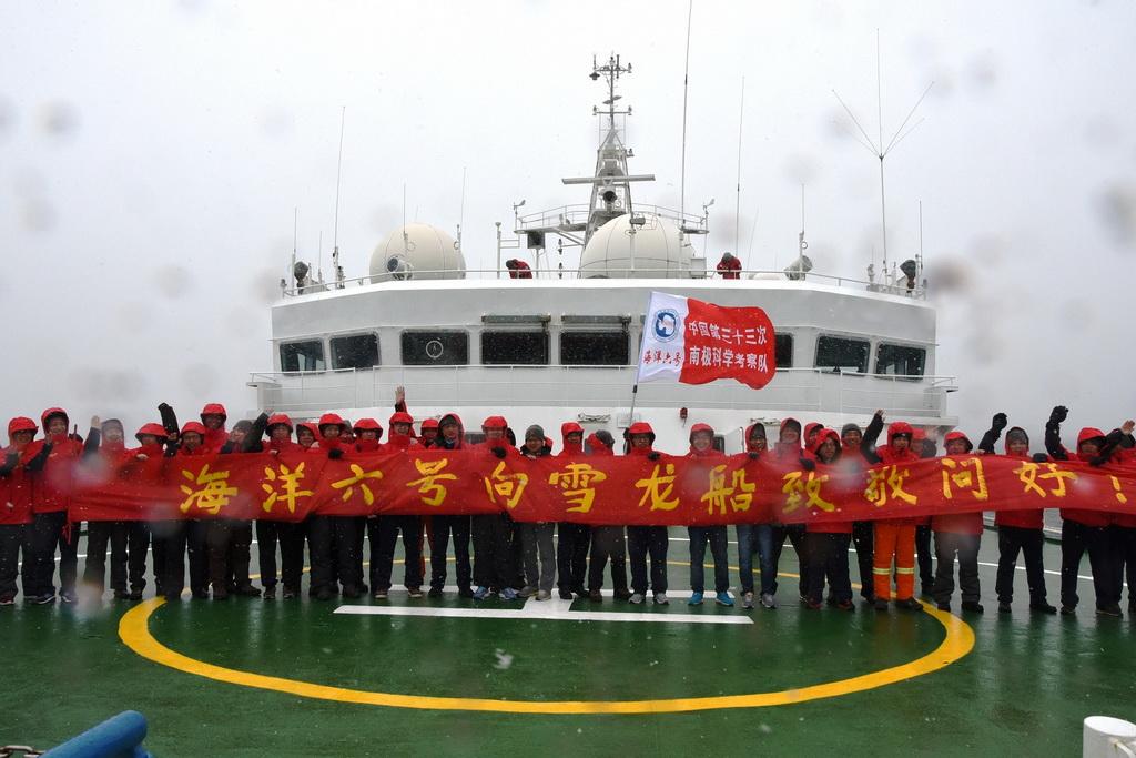 """北京时间2017年1月6日凌晨,""""海洋六号""""科考队员在南极海域打出横幅向""""雪龙""""号致意。 新华社记者 王攀 摄"""